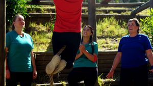 Women applauding female trainer while rope climbing
