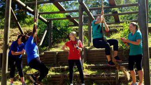 Female trainer assisting women in rope climbing