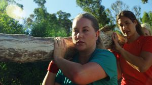 Group of fit women carrying a heavy wooden log during obstacle course