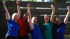 Portrait of happy women cheering during obstacle course