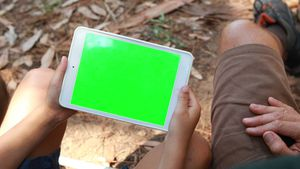 Father and son using digital tablet outside tent