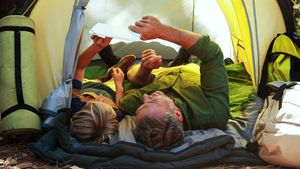 Father and daughter using digital tablet outside tent