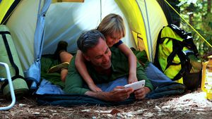 Father and son using mobile phone outside tent