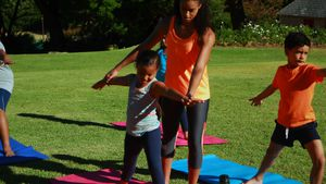 Yoga instructor instructing children in performing exercise