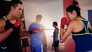 Coach training a woman with boxing