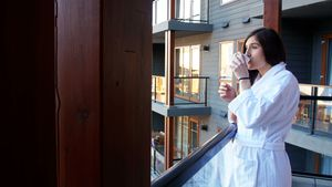 Woman having a cup of coffee in balcony