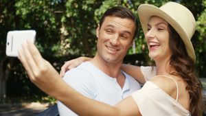 Couple taking a selfie on mobile phone near car