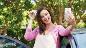 Woman taking a selfie on mobile phone near car