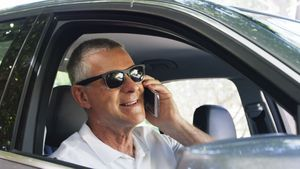 Senior man talking on mobile phone in the car