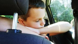 Boy relaxing in the back seat of car