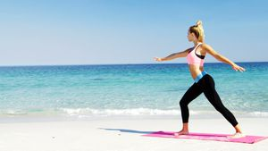 Fit woman doing stretching exercise at beach