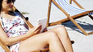 Beautiful woman listening to music on digital tablet at beach