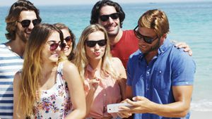 Friends taking a selfie on mobile phone at beach