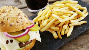 Hamburger, french fries and cold drink on slate board