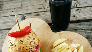 Hamburger, french fries and cold drink on wooden board