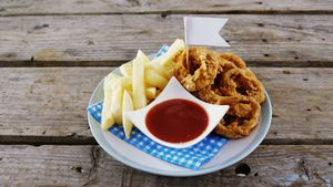 Onion ring and french fries with ketchup arranged in plate