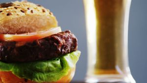 Beer and hamburger against grey background