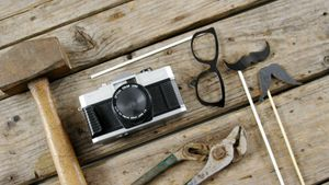 Work tool, Vintage camera, spectacles and fake mustache arranged on wooden plank