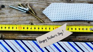 Happy fathers day card, tie, screw, measuring tape on wooden plank