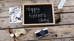 Happy fathers day message, vintage camera, photograph on wooden plank