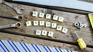 Happy fathers day block and old work tool arranged on wooden plank