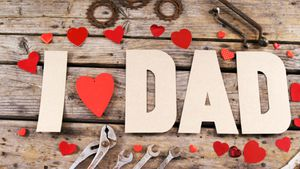 Text I love dad with red hearts and old work tool on wooden plank