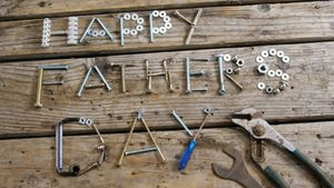 Happy fathers day text with various work tool arranged on wooden plank
