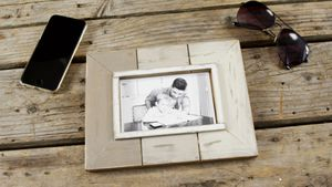Photo frame, sunglasses and mobile phone on wooden plank
