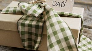 Tied gift box and happy fathers day card on wooden plank