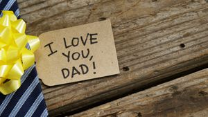 Decorated tie with happy fathers day card on wooden plank