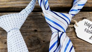 Ties arranged with happy fathers day tag on wooden plank