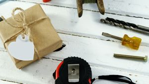 Gift box with working tools and fishing equipment on wooden plank