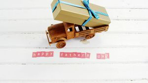 Toy truck with gift and happy fathers day blocks arranged on wooden plank