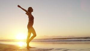Woman with arms outstretched walking on beach