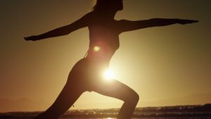 Silhouette of woman doing yoga on the beach