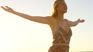 Woman with arms outstretched standing on the beach