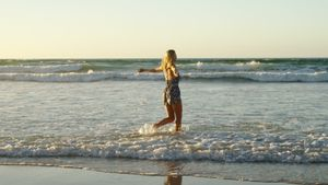 Woman with arms outstretched playing in water at beach