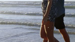Couple walking together on shore at beach