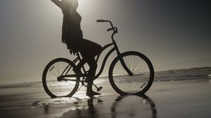Silhouette of woman sitting with arms outstretched on bicycle