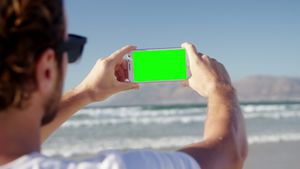 Man taking photo with mobile phone at beach