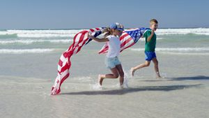 Siblings holding American flag while running on shore at beach