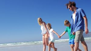 Family holding hands while walking on shore at beach