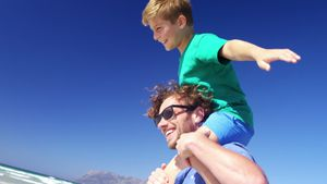 Father carrying son on his shoulders at beach