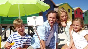Family taking selfie on mobile phone at beach