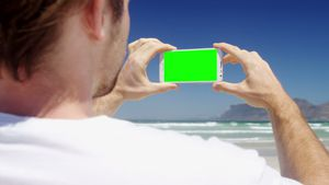 Man taking photo from mobile phone at beach