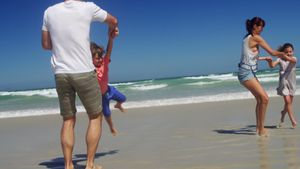 Parents playing with their kids at beach