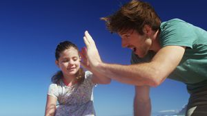 Happy family giving high five to each other at beach