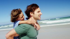 Father giving piggyback to his son at beach