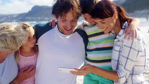 Multi generation family using mobile phone at beach