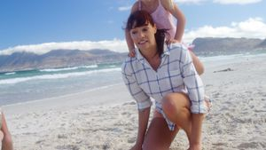 Mother giving piggyback ride to her daughter at beach